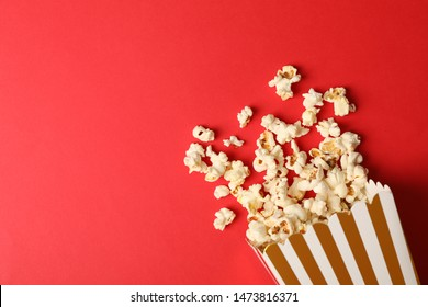 Flat lay composition with striped box and popcorn on color background