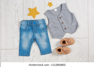 Flat lay composition with stylish child clothes and shoes on wooden background