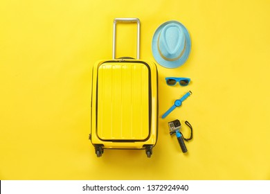 Flat lay composition with suitcase and accessories on color background