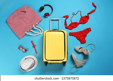 Flat lay composition with suitcase and accessories on color background. Summer vacation