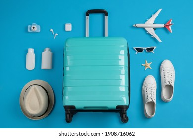 Flat lay composition with suitcase and travel accessories on light blue background. Summer vacation