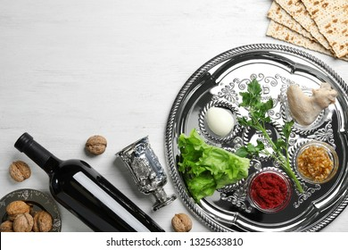Flat lay composition with symbolic Passover (Pesach) items and meal on wooden background, space for text