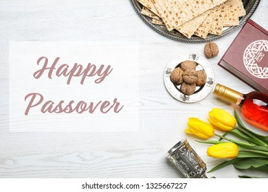 Flat lay composition of symbolic Pesach items on wooden background. Happy Passover
