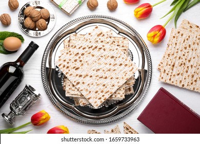 Flat lay composition with symbolic Pesach (Passover Seder) items on white wooden table