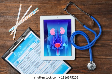Flat lay composition with tablet, stethoscope and test form on wooden background. Urology concept