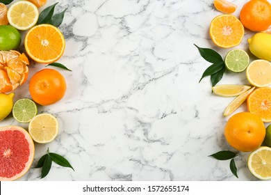 Flat lay composition with tangerines and different citrus fruits on white marble background. Space for text