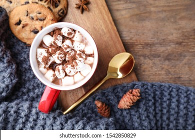 Flat lay composition of tasty cocoa with marshmallows on wooden table. Space for text
