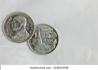 Flat lay composition of Thailand 1 Baht silver coin with head and tail on white space background ( Thai alphabet means value of 1 baht )