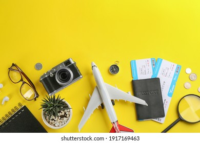 Flat lay composition with toy airplane and travel items on yellow background. Space for text