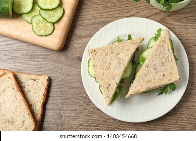 Flat lay composition with traditional English cucumber sandwiches and ingredients on wooden background