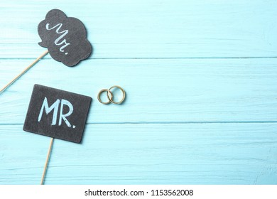 Flat lay composition with wedding rings and photo booth props on wooden background. Gay marriage
