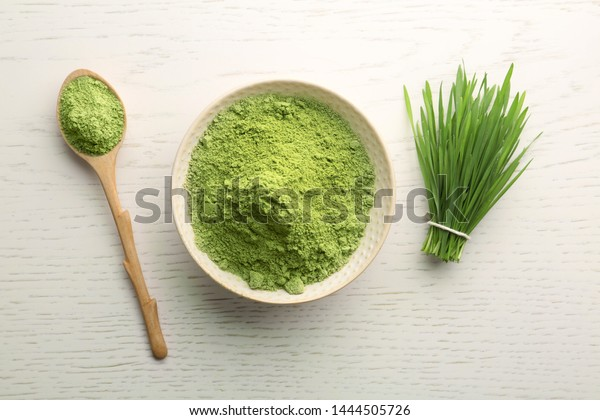 Flat lay composition with wheat grass powder on white wooden table