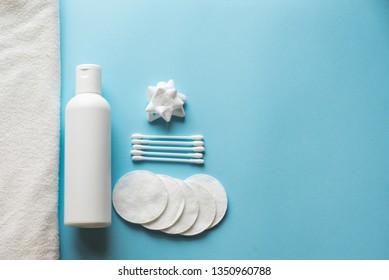Flat lay composition with white bottle, cotton swabs and pads, flower , towel on blue background. body skin care concept . copy space