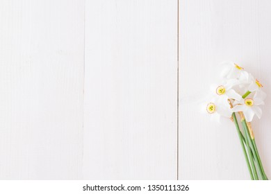 Flat lay composition with white daffodils on a white wooden table