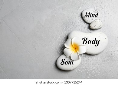 Flat lay composition of zen stones with words Mind, Body, Soul on light background. Space for text