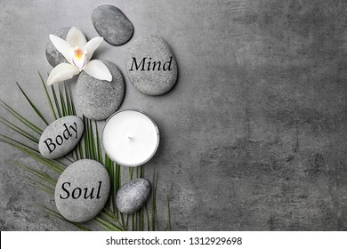Flat lay composition of zen stones with words Mind, Body, Soul on grey background. Space for text