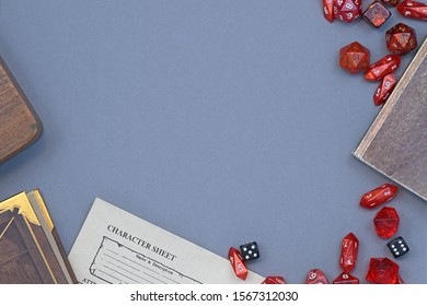 Flat lay concept design for tabletop role playing with cred RPG dices, character sheet and rule books with empty copy space on gray background
