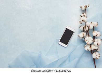 Flat lay concept of feminine light blue background with cell phone, silk and branch of artificial cotton flower. Top view with copy space.