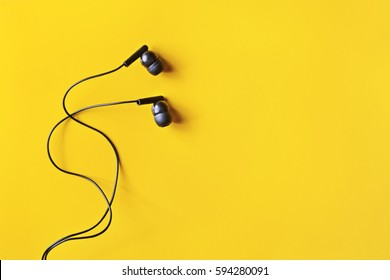 Flat lay concept: headphones on pastel backgrounds. Black headphones on a yellow background, top view, copyspace. Trendy colorful photo. Minimal style with colorful paper backdrop.