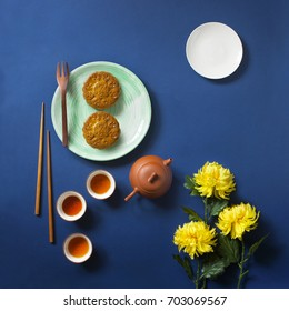 "Flat lay conceptual mid autumn festival theme mooncake tea party table top shot on moody blue background. Translation on round moon cake ""Mid autumn""."