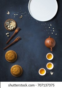 Flat lay conceptual mid-autumn festival food and drink mooncake and tea on rustic moody blue background. Text space image.
