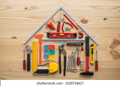 Flat lay of construction tools as house model on wooden background with copy space. New house construction, repair maintenance, DIY (Do It Yourself) and real estate property or finance loan concept.