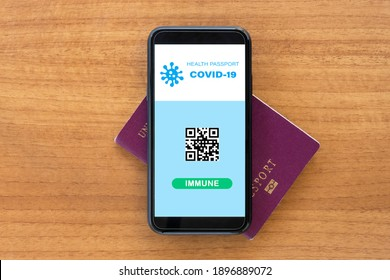 Flat lay with copy space, a smart phone with a digital illustration of a Covid-19 Health Passport concept is arranged on a passport. Travel concept during the Covid-19 pandemic.
