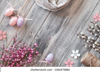 Flat lay with copy-space  on dark wooden surface with spring decorations: Easter eggs, pink flowers, pussy willow and linen towel