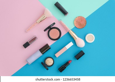 Flat lay Cosmetics for makeup, brush, highlighter, concealer, makeup, lipstick, primer, blush on pink, blue and mint tri color vibrant background. Top view.