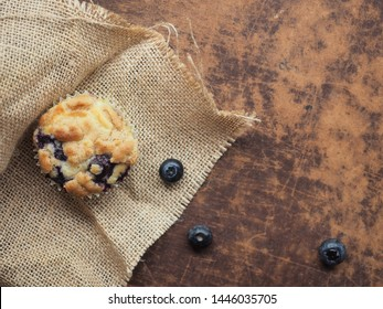 Flat lay of crumble blueberry muffin on sackcloth on wood background