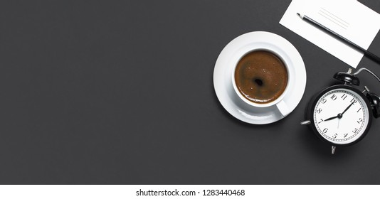 Flat lay cup of black coffee, black alarm clock, pencil, white cards on gray dark background top view copy space. Minimalistic food concept, morning breakfast, time to work hot drink coffee background