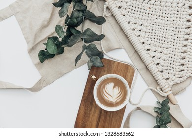 Flat lay Cup of coffee on wooden serving tray and eucalyptus branch with macrame decoration. Minimal bohemian lifestyle concept for blog and social media