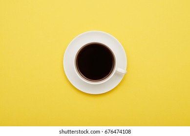 Flat lay of cup of coffee on yellow background with copy space