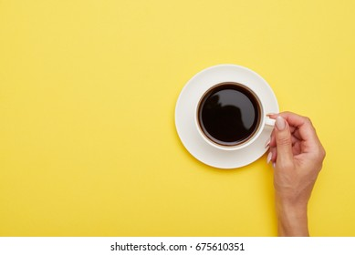 Flat lay of cup of delicious coffee in woman hand on yellow background with copy space