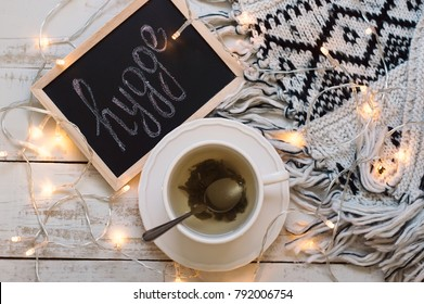 "Flat lay with cup of green tea, blackboard with chalk written word ""hygge"", yellow lights and woolen blanket on wooden background. Hygge lifestyle. Cozy and comfortable atmosphere"