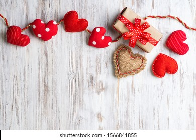 Flat lay cute composition with handmade fabric red hearts. Gift box with ribbon bow on wooden table. Happy birthday or anniversary congratulation. Romantic message template with copy space.