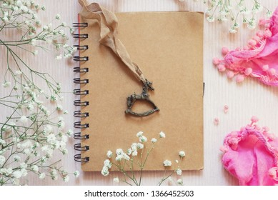 flat lay: cute diary with kraft cover, vintage pendant in the shape of a horse, white flowers and a light summer pink scarf. Concept: happy memories and dreams