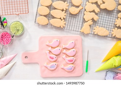 Flat lay. Decorating Easter sugar cookies with rotal icing.