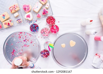 Flat lay. Decorating heart shape sugar cookies with royal icing and pink sprinkles for Valentine's day.
