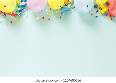 Flat lay decoration party concept on pastel blue background with border top view