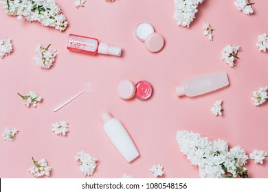 Flat lay of decorative cosmetic and creams in frame made of lilac flowers on pink background. Beautiful cosmetic set. Top view.