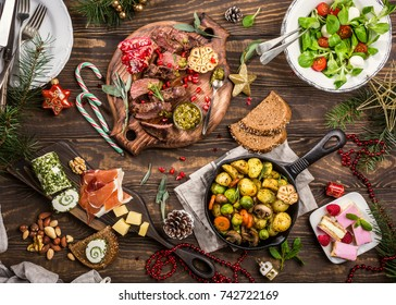 Flat lay of Delicious Christmas themed dinner table with roasted meat steak, appetizers and desserts. Top view. Holiday concept.