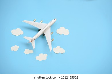 Flat lay design of travel concept with plane and cloud on blue background with copy space.