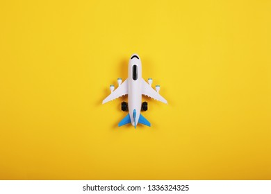 Flat lay design of travel concept with plane on yellow background with copy space. Summer vacation.