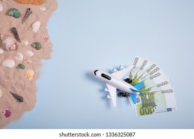 Flat lay design of travel concept with plane, banknotes of euros, money on blue background with copy space. Summer vacation, sea coast, beach. Expenses on a holiday.
