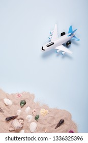 Flat lay design of travel concept with plane on blue background with copy space. Summer vacation, sea coast, beach.