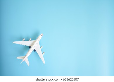 Flat lay design of travel concept with plane on blue background with copy space.