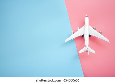 Flat lay design of travel concept with plane on blue and pink background with copy space.