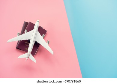 Flat lay design of Travel concept with plane and passport on pink and blue pastel background with copy space.