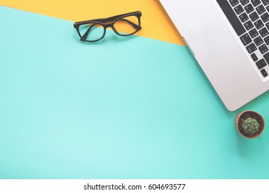 Flat lay design of work desk with notebook, eye glasses and cactus on green and yellow background.
